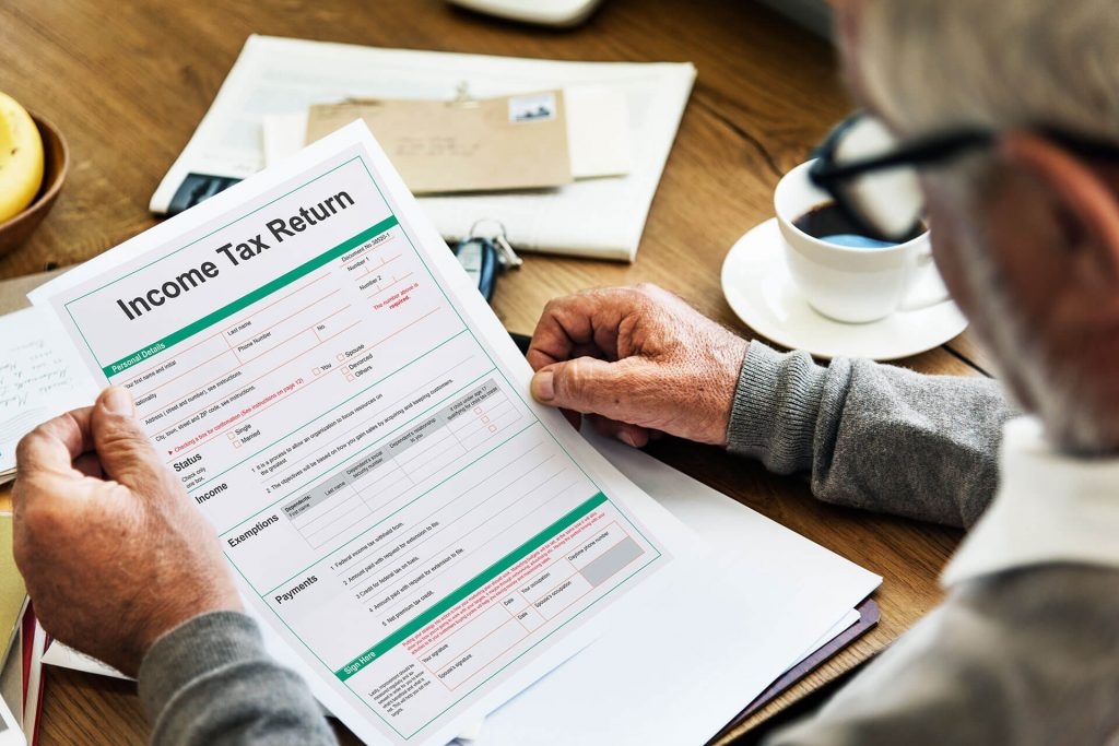man reading income tax return document