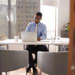 Male Financial Advisor In Modern Office Sitting At Desk Working On Laptop