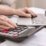 person calculating tax return using a calculator and laptop